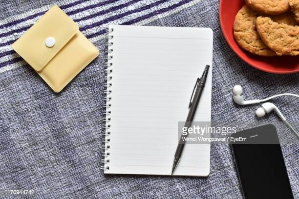 high angle view of pen on note pad amidst smart phone and cookies over fabric - wimol wongsawat stock photos and pictures