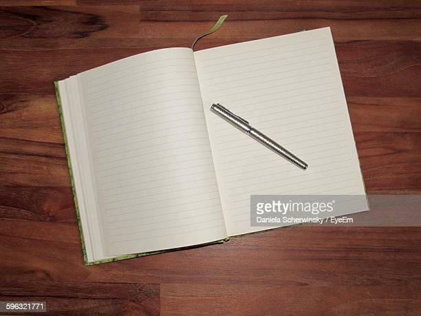 High Angle View Of Pen With Blank Notebook On Table
