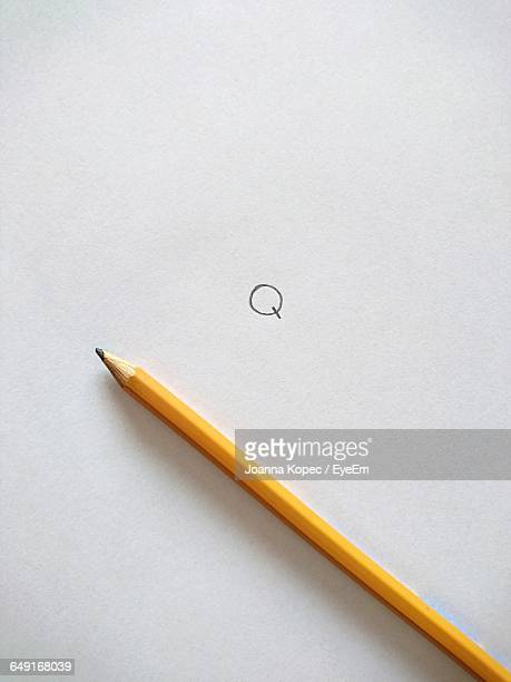 High Angle View Of Pencil On Paper With Letter Q