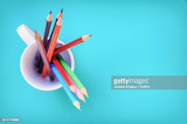 high angle view of pencils in cup over blue background - fourniture de bureau photos et images de collection
