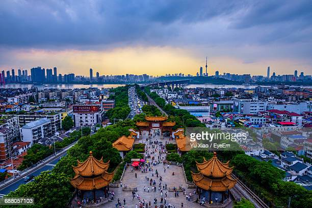 high angle view of people amidst gazebos against cloudy sky during sunset in city - wuhan stock photos and pictures