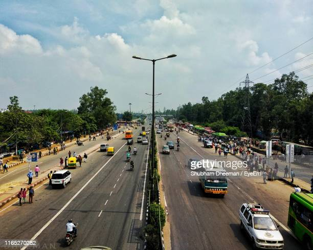 high angle view of people and vehicles on road against sky - motorway stock pictures, royalty-free photos & images