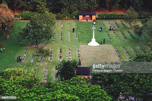 high angle view of people and white cross on field in cemetery - chittagong stock pictures, royalty-free photos & images
