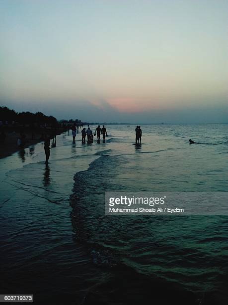 High Angle View Of People At Beach Against Sky During Sunset