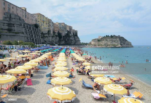 high angle view of people at beach against sky - calabria stock pictures, royalty-free photos & images