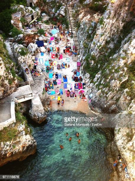 high angle view of people at beach by rock formations - les pouilles photos et images de collection