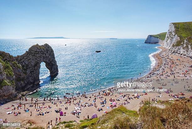 high angle view of people at durdle door beach against clear blue sky - southampton england stock pictures, royalty-free photos & images