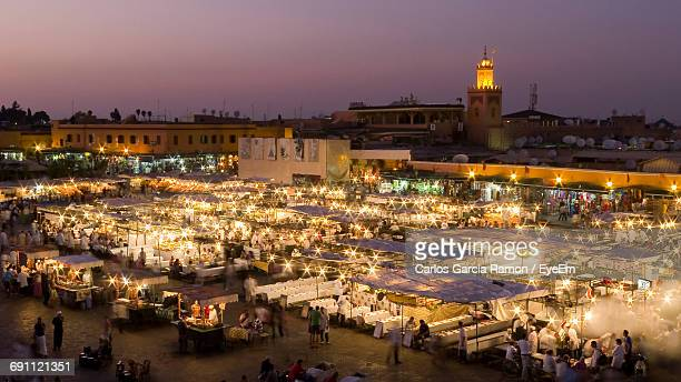 high angle view of people at illuminated djemma el fna square during dusk - djemma el fna square stock photos and pictures