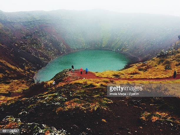 high angle view of people at kerid in volcanic crater during foggy weather - selfoss stock photos and pictures