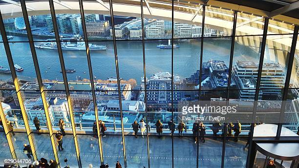 High Angle View Of People At Observation Point Seen Through Glass