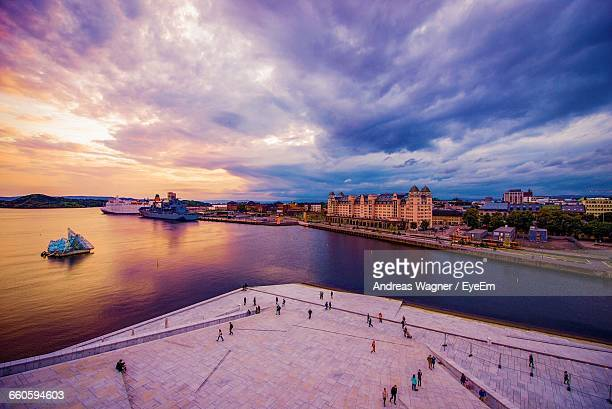 high angle view of people at oslo opera house against cloudy sky - oslo stock pictures, royalty-free photos & images