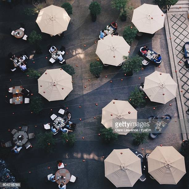 high angle view of people at sidewalk cafe - pavement cafe stock pictures, royalty-free photos & images