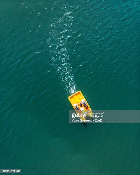 high angle view of people boating on sea - pedal boat stock pictures, royalty-free photos & images
