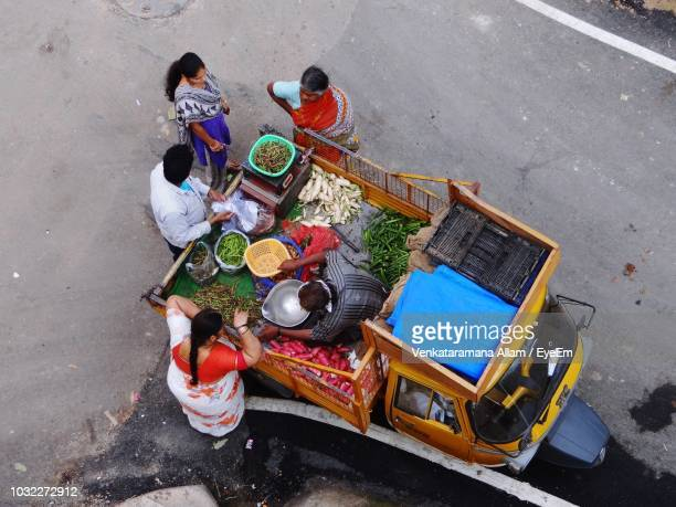 high angle view of people buying vegetables from vendor on street - bangalore stock pictures, royalty-free photos & images