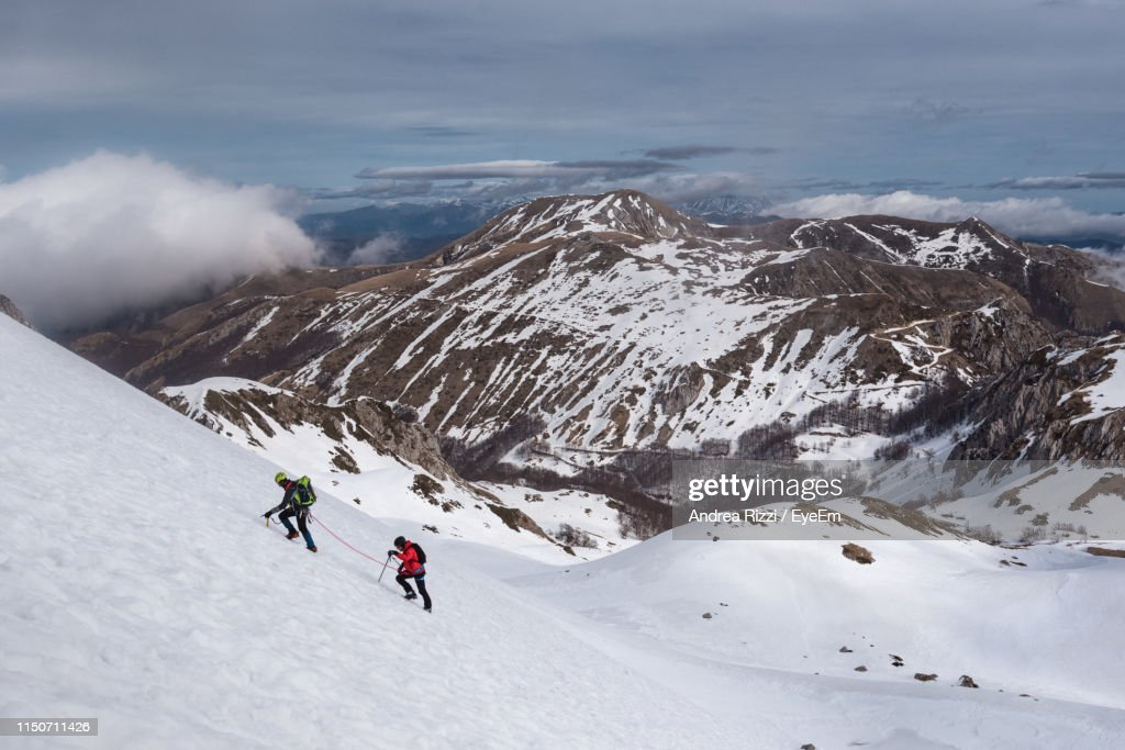 High Angle View Of People Climbing Snow Covered Mountain : Foto stock