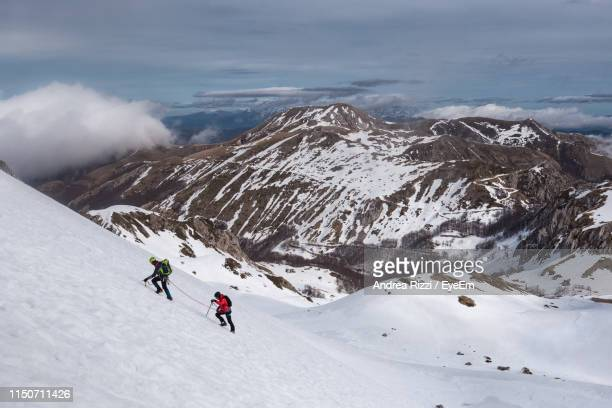 high angle view of people climbing snow covered mountain - andrea rizzi stockfoto's en -beelden
