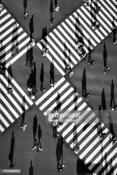 high angle view of people crossing street - zebra crossing stock pictures, royalty-free photos & images