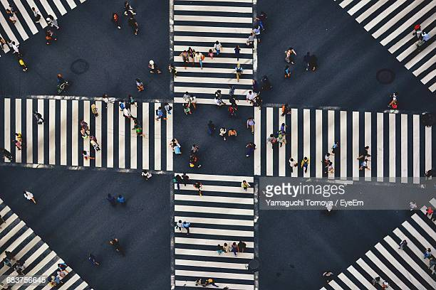 high angle view of people crossing the street - pedestrian crossing stock photos and pictures