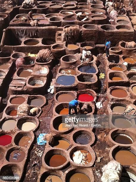 High Angle View Of People Dyeing Fabrics In Containers