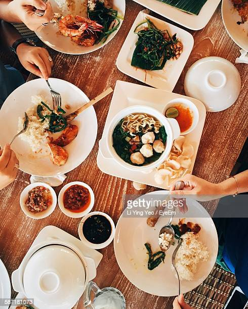High Angle View Of People Eating Food At Dining Table