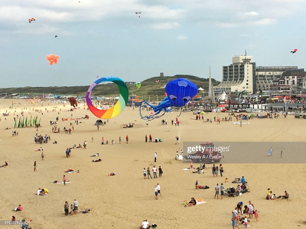 High Angle View Of People Enjoying At Beach Against Sky : Stock Photo