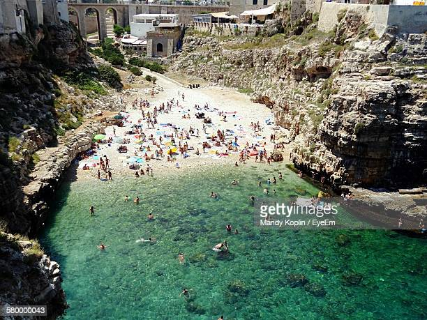 high angle view of people enjoying at beach - polignano a mare stock photos and pictures