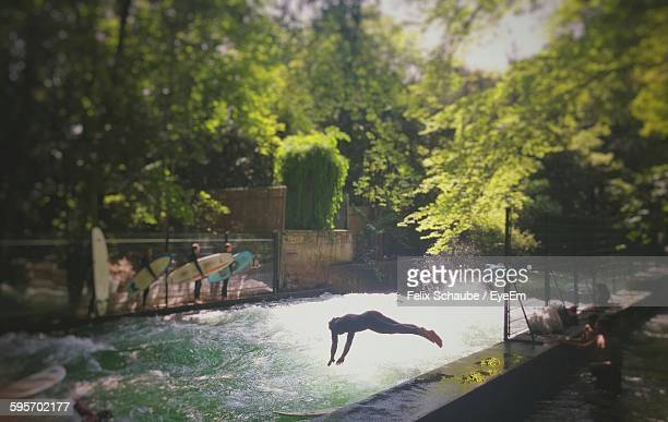high angle view of people enjoying at eisbach river - münchen stock-fotos und bilder