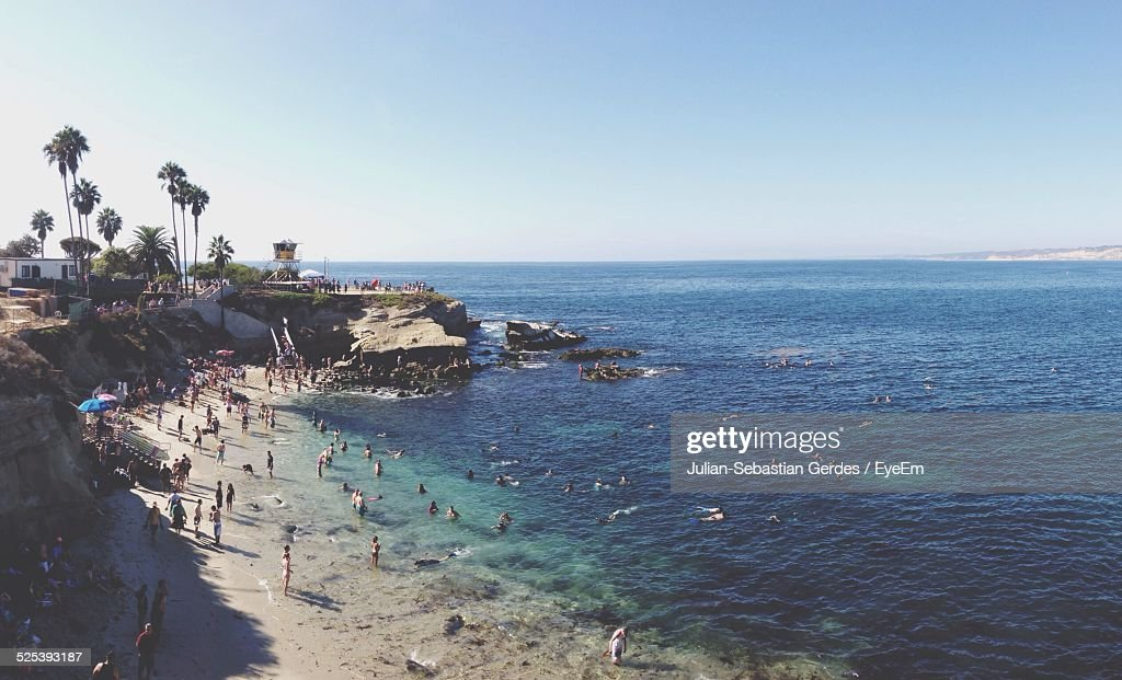 High Angle View of People Enjoying At Sea Shore Against Clear Sky : Stock Photo