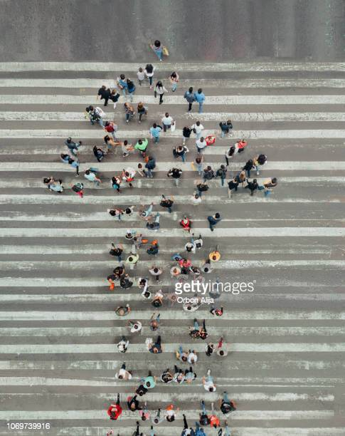 high angle view of people forming and arrow on the street - abundance stock pictures, royalty-free photos & images