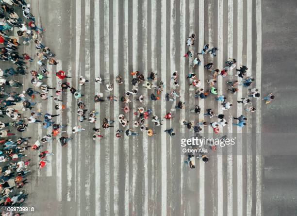 high angle view of people forming and arrow on the street - leading stock pictures, royalty-free photos & images