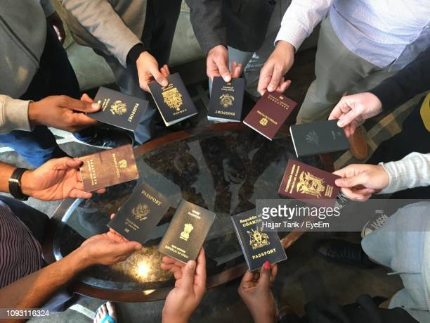 high angle view of people holding passports over table - passport stock pictures, royalty-free photos & images