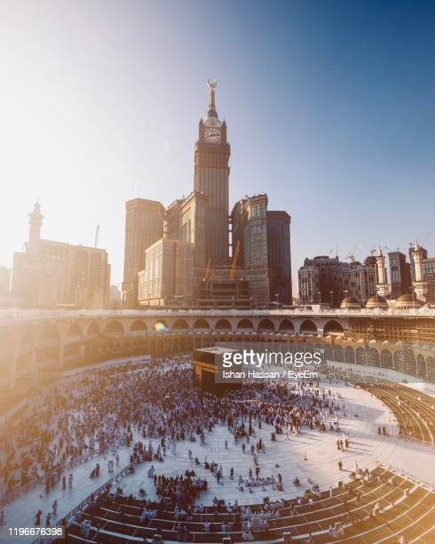 high angle view of people in mecca by modern buildings against clear sky - mecca stock pictures, royalty-free photos & images