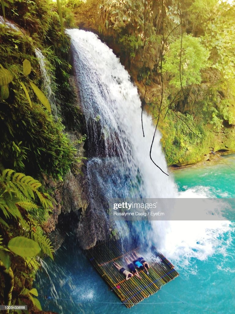 High Angle View Of People Lying On Wooden Raft Below Waterfall : Stock Photo