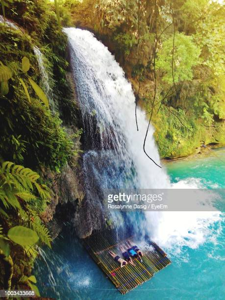 High Angle View Of People Lying On Wooden Raft Below Waterfall
