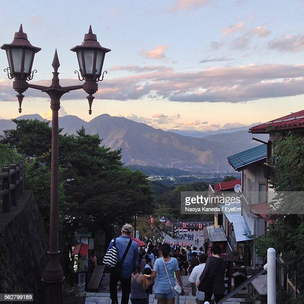 high angle view of people moving down steps against cloudy sky - maebashi city stock photos and pictures
