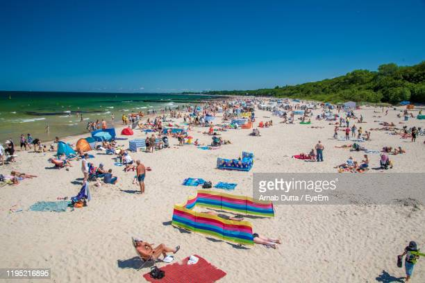 high angle view of people on beach against clear blue sky - pologne photos et images de collection