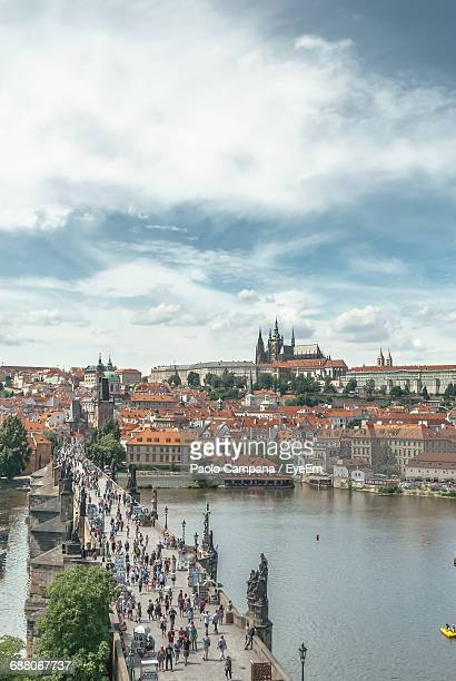 High Angle View Of People On Charles Bridge Over Vltava River Against Cloudy Sky