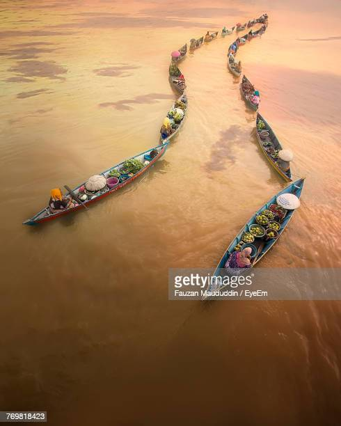 High Angle View Of People On Floating Market At River During Sunset