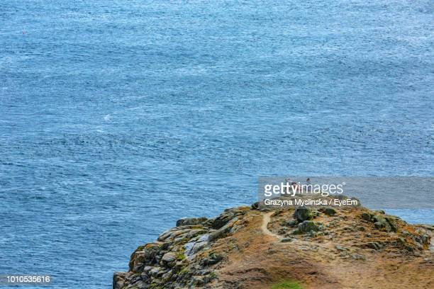 High Angle View Of People On Rocks Against Sea