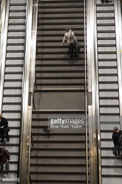 High Angle View Of People On Stairway Amidst Escalators At Railroad Station