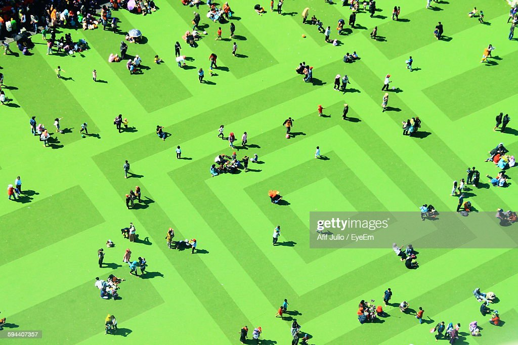 High Angle View Of People On Textured Green Field : Stock Photo