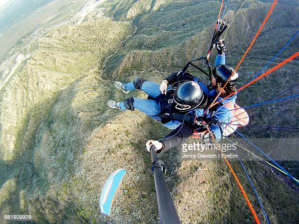 High Angle View Of People Paragliding Over Mountains