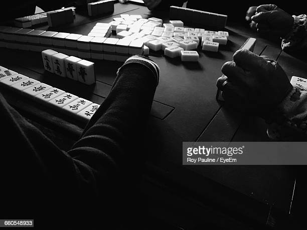 high angle view of people playing mahjong at table - mahjong stock photos and pictures