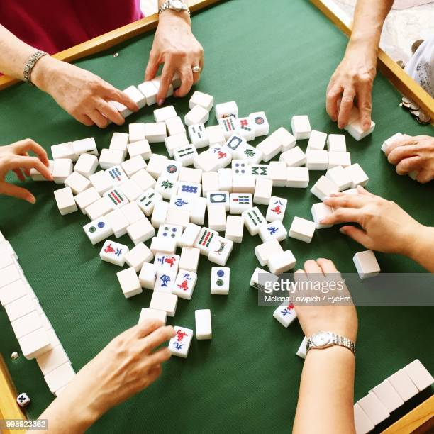 high angle view of people playing with mahjong tiles on table - mahjong stock photos and pictures