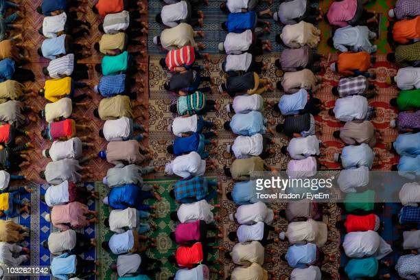 high angle view of people praying in mosque - muslim praying stock pictures, royalty-free photos & images