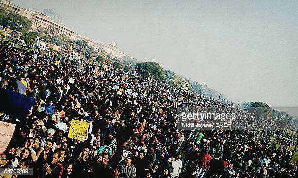 high angle view of people protesting at rally against sky - protestor stock pictures, royalty-free photos & images