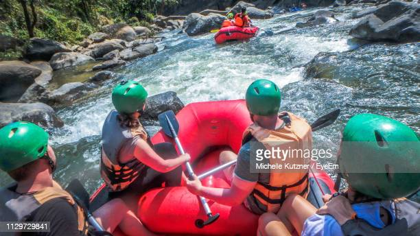 high angle view of people rafting river - ウオータースポーツ ヘルメット ストックフォトと画像