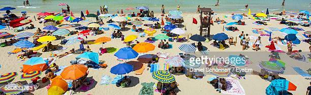 High Angle View Of People Relaxing Under Parasols At Beach