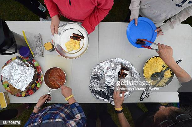 High Angle View Of People Serving Food At Table