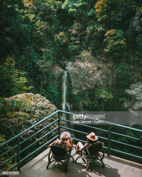 High Angle View Of People Sitting At Observation Point Against Waterfall